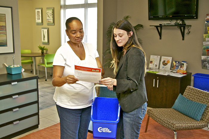 ARR employee holds a recycling bin and shows woman a paper explaining the URO.