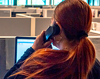 woman working in the Austin code department office answering a phone call. She has shiny red hair, is wearing a black sweater, and is holding the phone up to her left ear