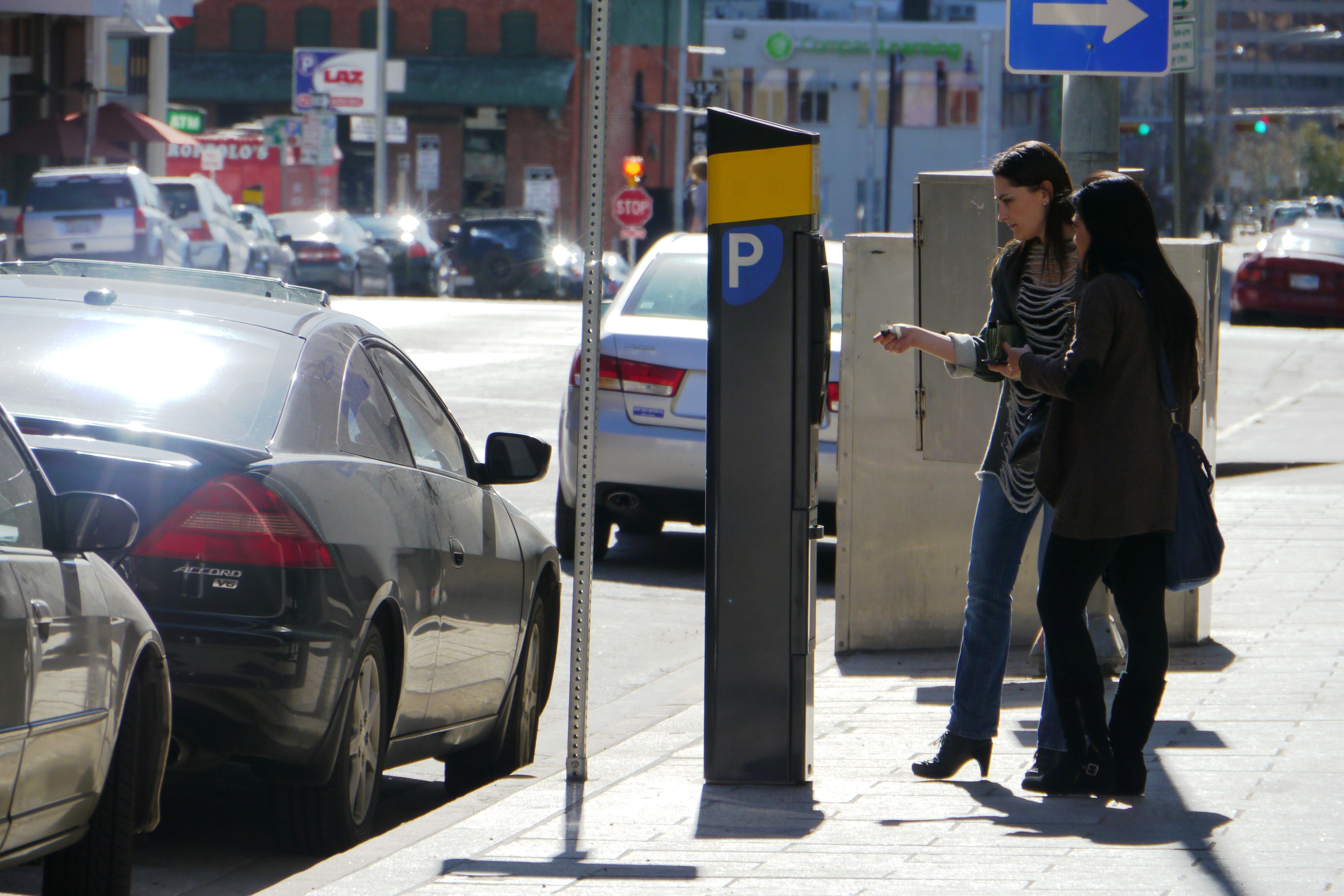 An adult paying for an on-street parking space at a parking kiosk