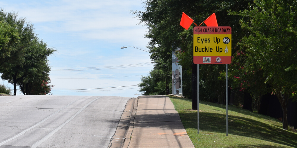 "Photo of a sign on Pleasant Valley Road at Oltorf Street that says ""High-Crash Roadway. Eyes up, Buckle up"""