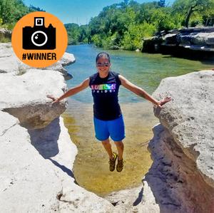 photo of girl balancing between two large rock ledges over lake