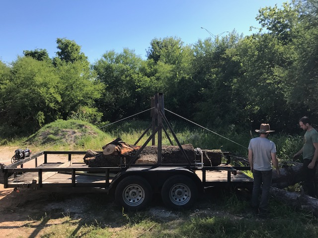 Photo of two people by a trailer with a log on it