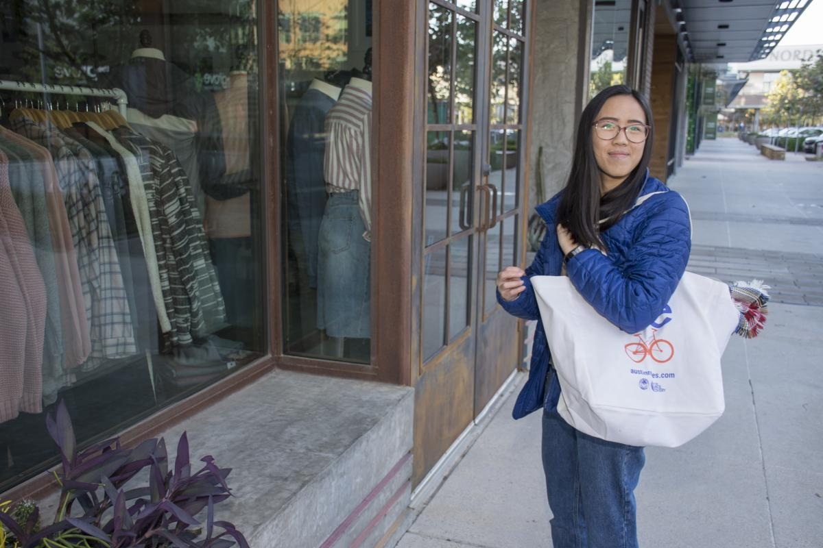Woman shops for clothing with her reusable bag