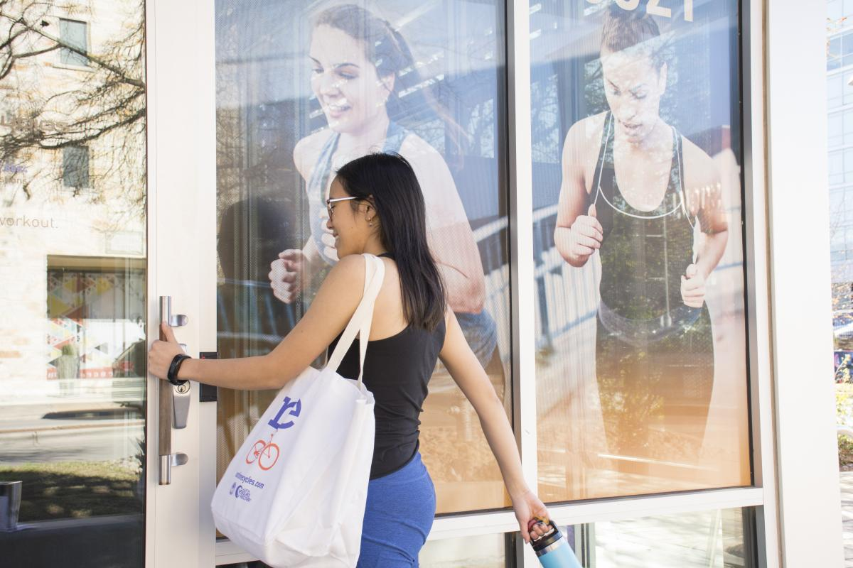 Woman opens the door to the gym, carrying her reusable water bottle and reusable bag
