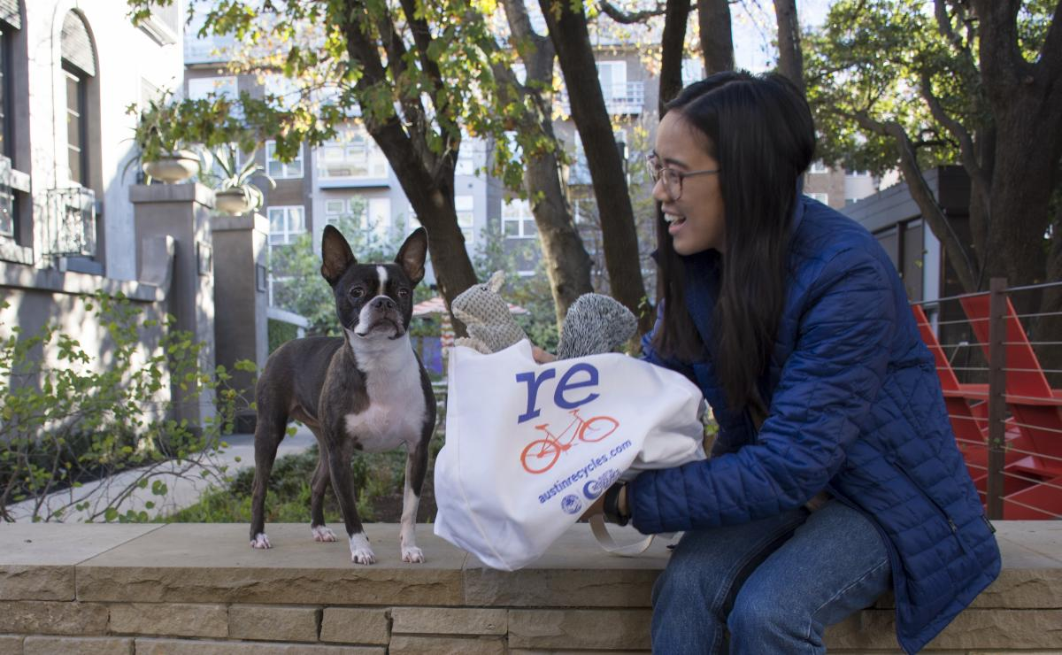 Woman presents a gift to her Boston Terrier in a reusable bag
