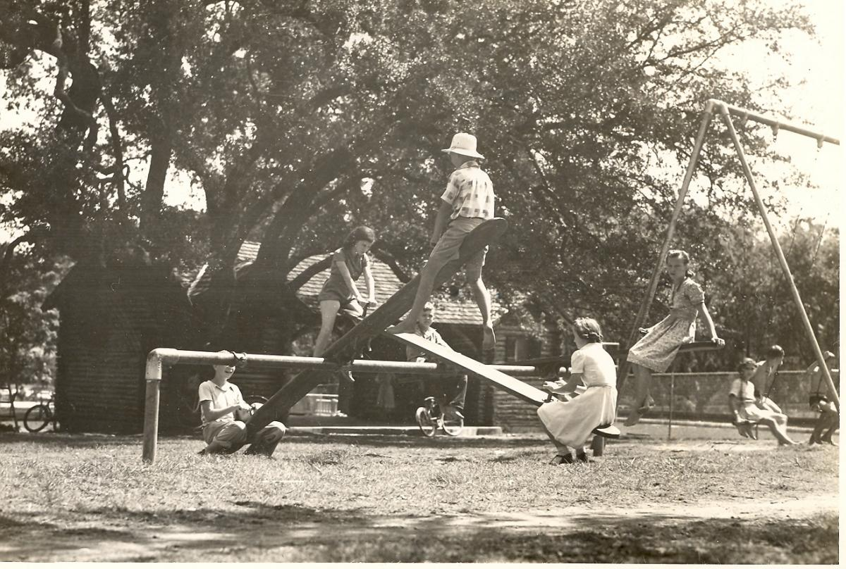 A black and white photo of hte Shipe Park playground in 1940. The playground is crowded with children playing on seesaws and swings. The log cabin shelter house is visible in the background.