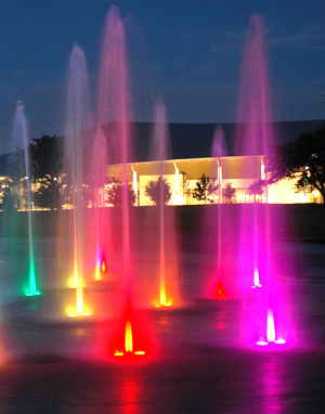 A photo of Butler Park's splash pad at night. Several jets of water shoot up from the ground and are lighted different colors: magenta, yellow, red, green and orange.