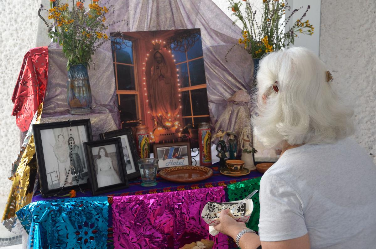 A woman gazes at the altar she created for Dia de Los Muertos.
