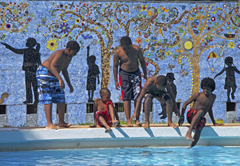 Five kids stand in front of the new mural at Shipe Park, getting ready to get into the pool.
