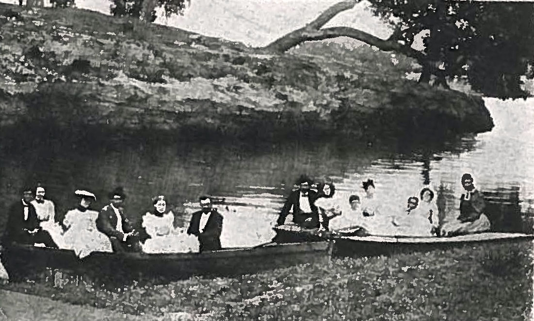 Barton Springs during the 1890s. 13 people sit in two boats, presumably on a rowing trip.