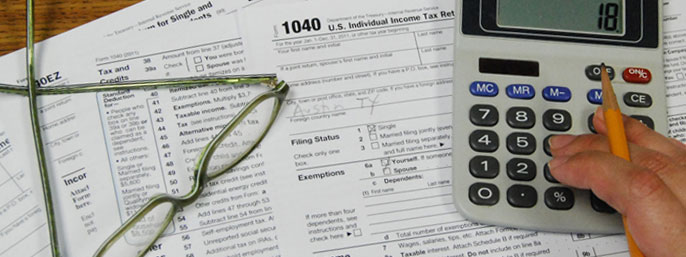 A calculator and pair of glasses rest on a pile of tax documents.