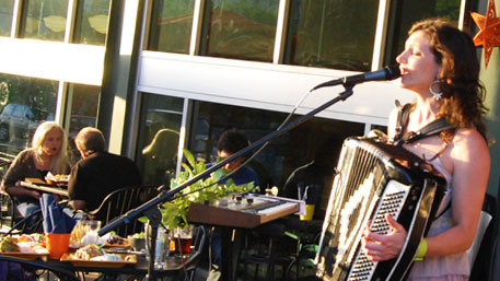 A band is playing  outdoors at a local restaurant.