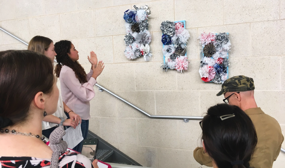 Students admire three floral looking three-dimensional art pieces hanging on a wall in a stairway.