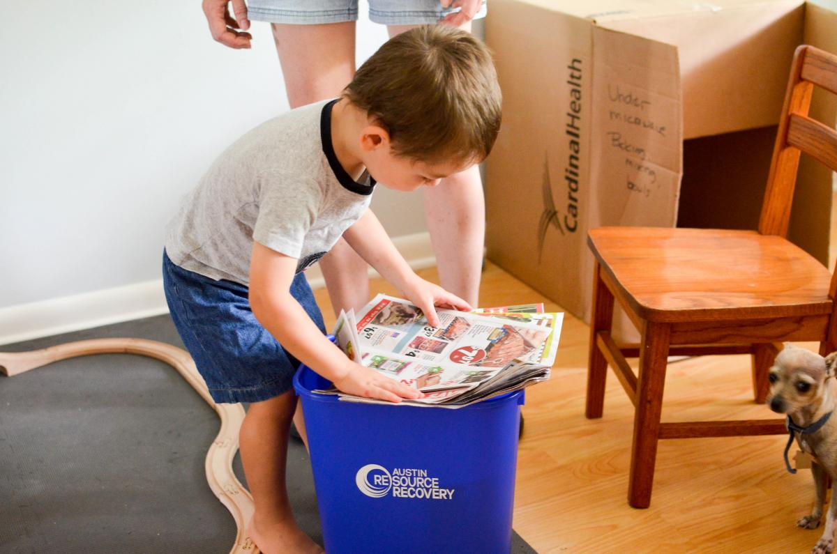 Image of Jennifer's son recycling paper.