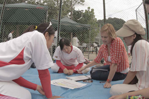 Allison Orr sits with Japanese Womens Baseball players on the field