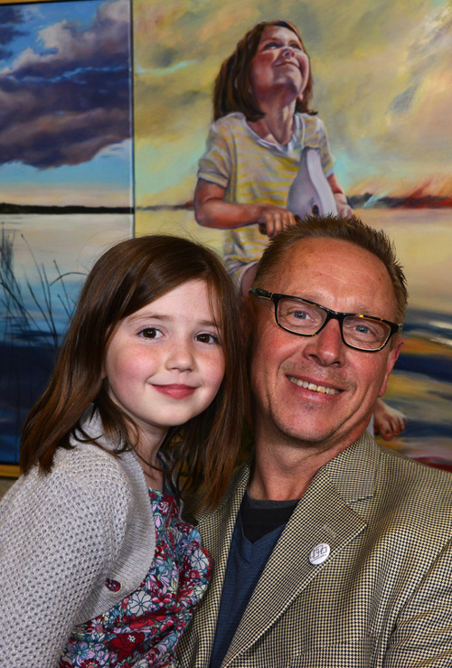 Artist Lawrence Jolly poses in front of his painting with his young model, Sedona.