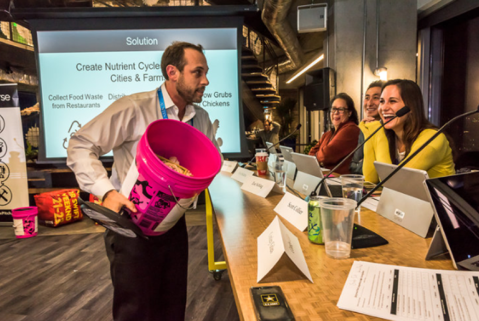 Rober Olivier of GrubTubs shows a sample food scrap collector to the 2016 [Re]Verse Pitch judges. Judges pictured, from front to back: Zoe Schlag, Kyle Ballarta and Rosa Rios Valdez.