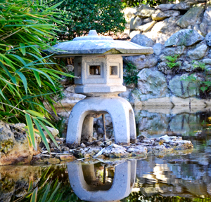 A japanese sculpture is reflected in clear pondwater at Zilker Botanical Garden.