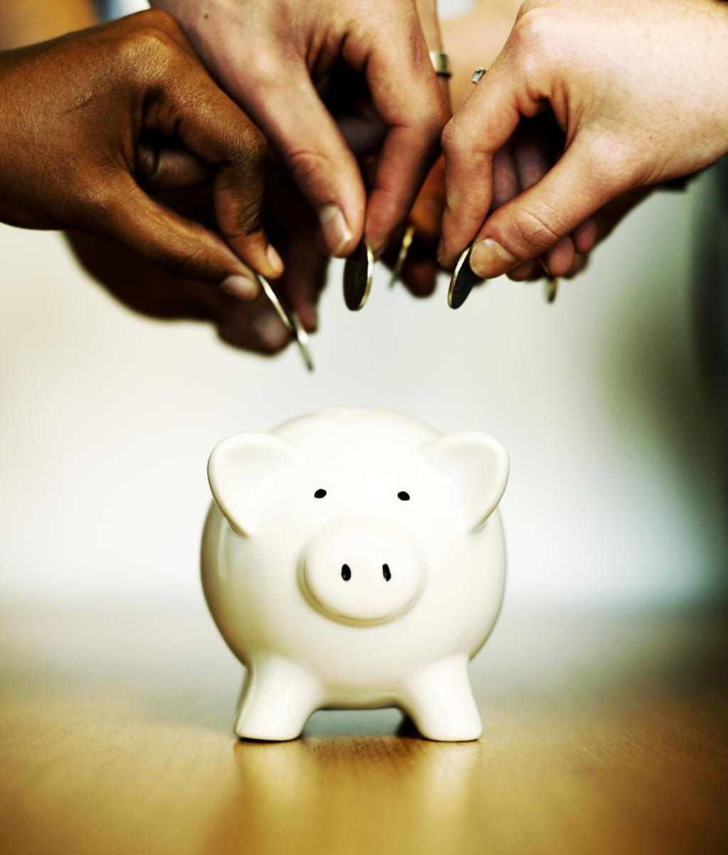 Picture of hands putting change in a piggybank