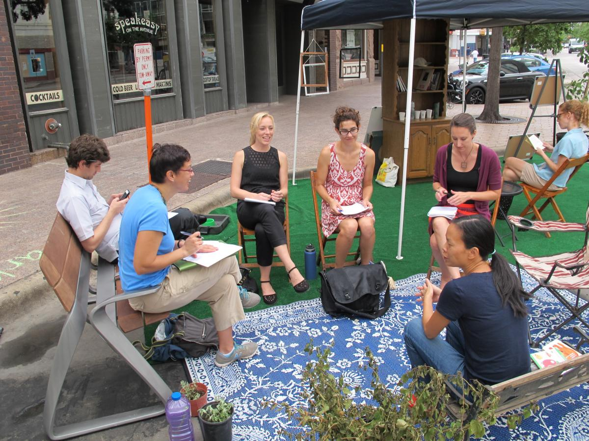 A group of colleagues gather for a meeting in the parklet.