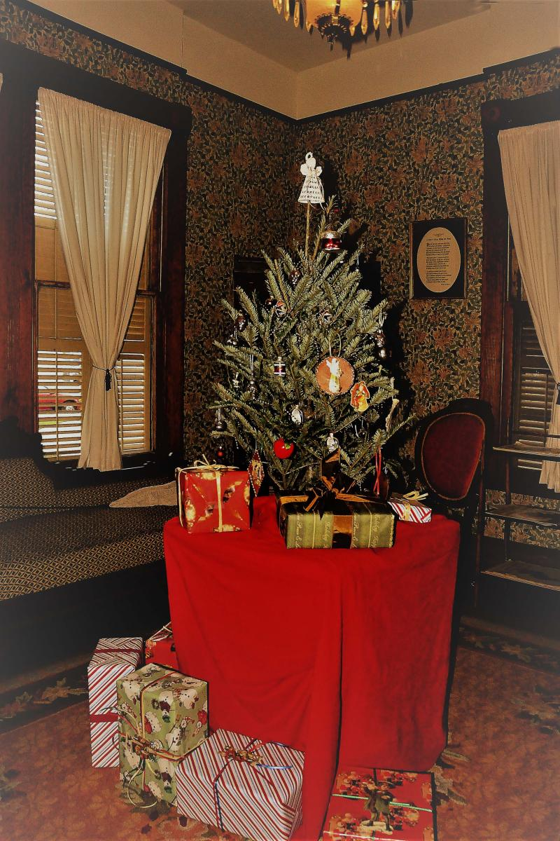 A color photograph showing a small Christmas tree sitting on a table surrounded by presents