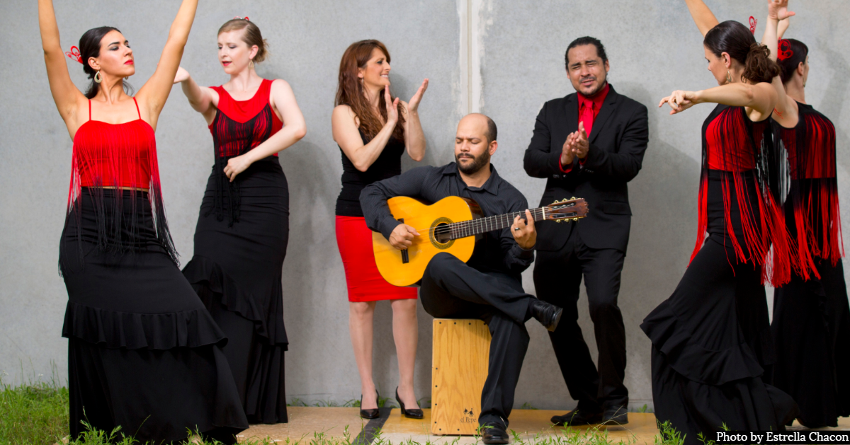 "Flamenco dancers dancing around a man seated playing the guitar. Photo credit reads ""Photo by Estrella Chacon"""