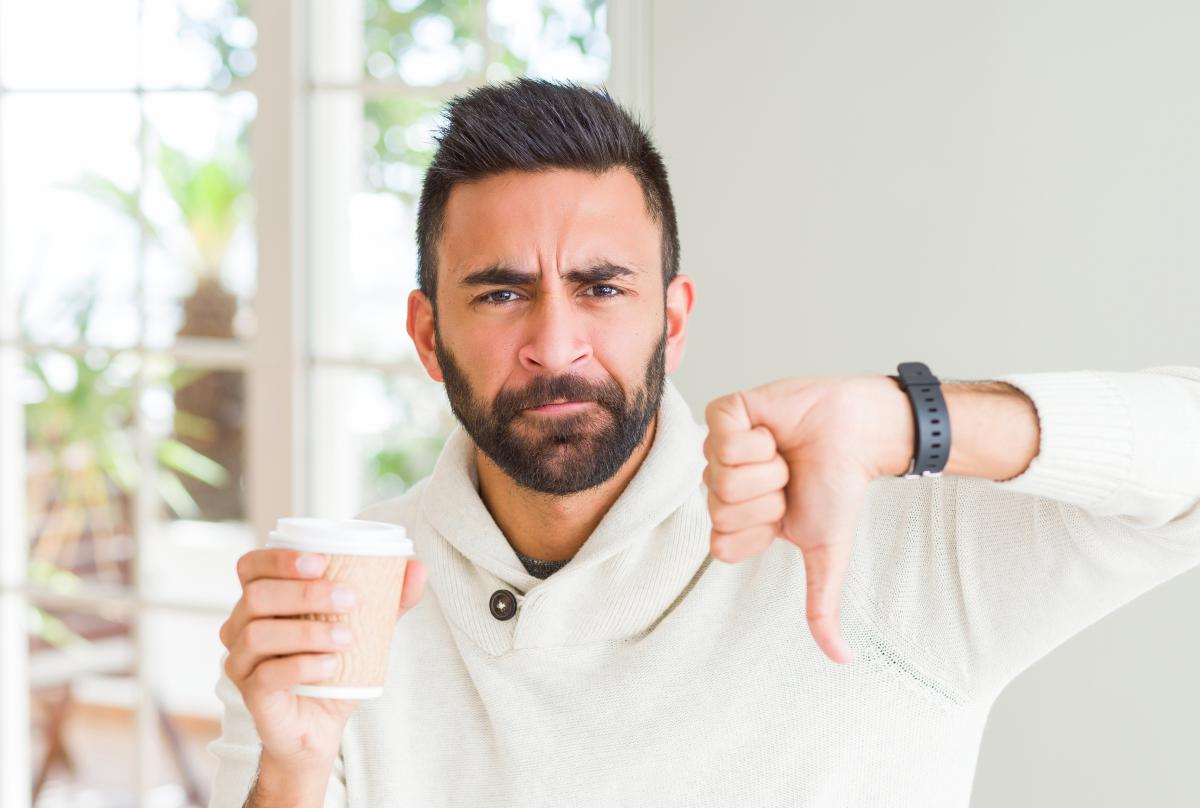 "Man holding a single-use coffee cup and giving ""thumbs down"""