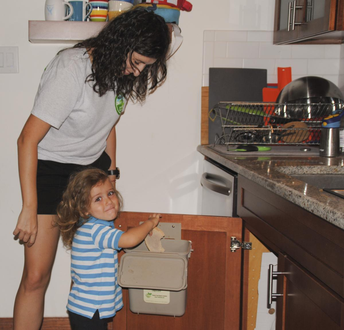Photo of Ellie with her son composting in the kitchen