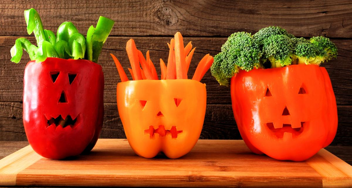Bell peppers cut into jack-o-lanterns and used to serve cut veggies in.