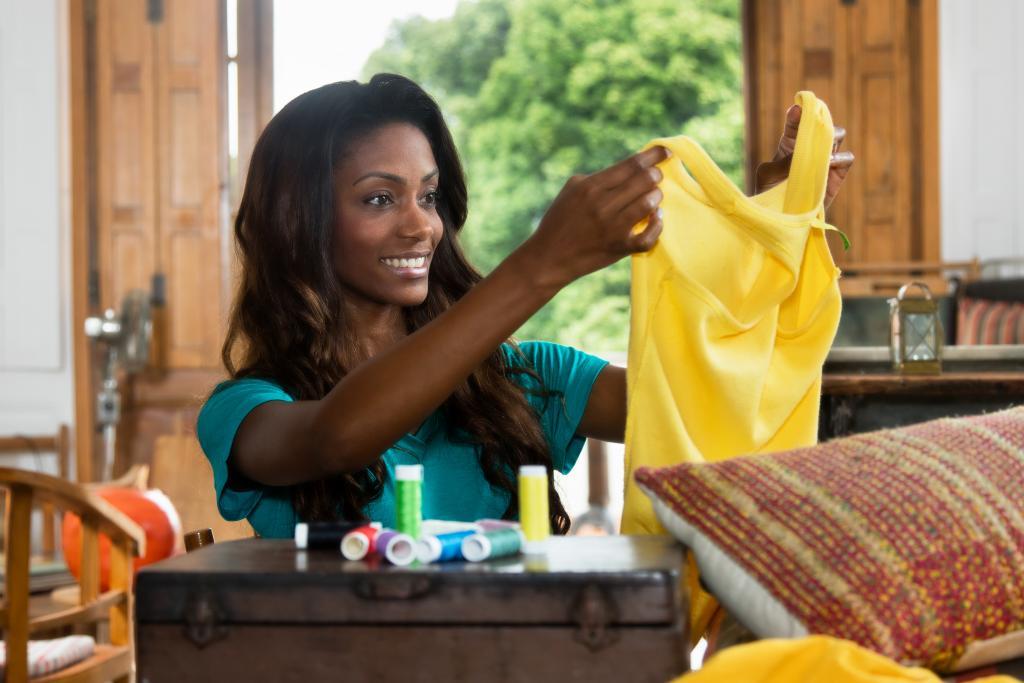 Woman uses a sewing machine to stitch a shirt
