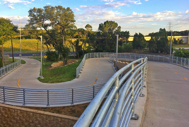 Winding concrete hike and bike trail with railings.