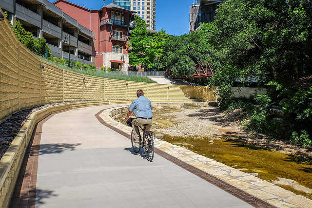 Cyclist riding on a concrete hike and bike path with a large retaining wall and high-rise buildings on the left.