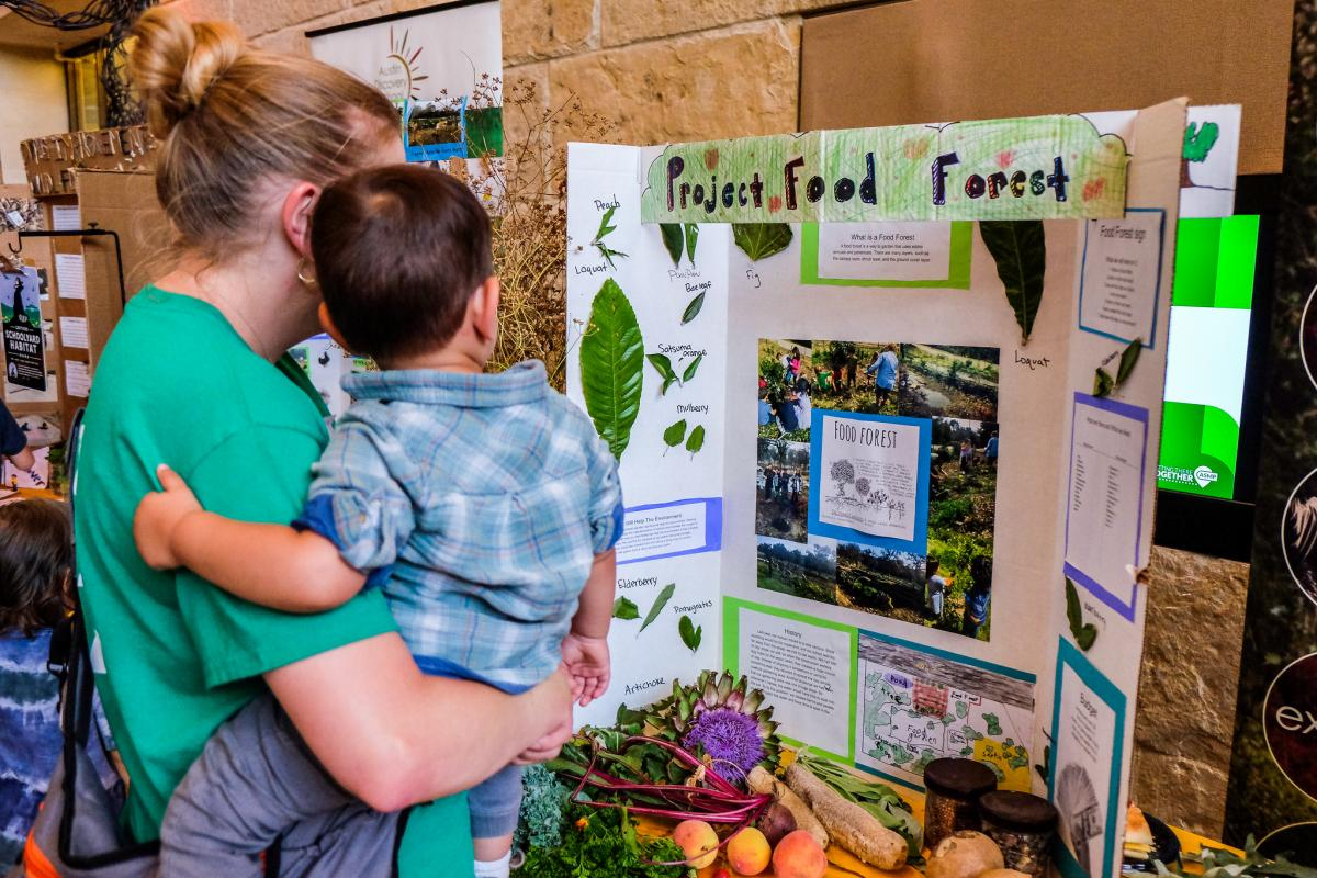"Mom and child looking at a student project display board titled ""Project Food Forest"""