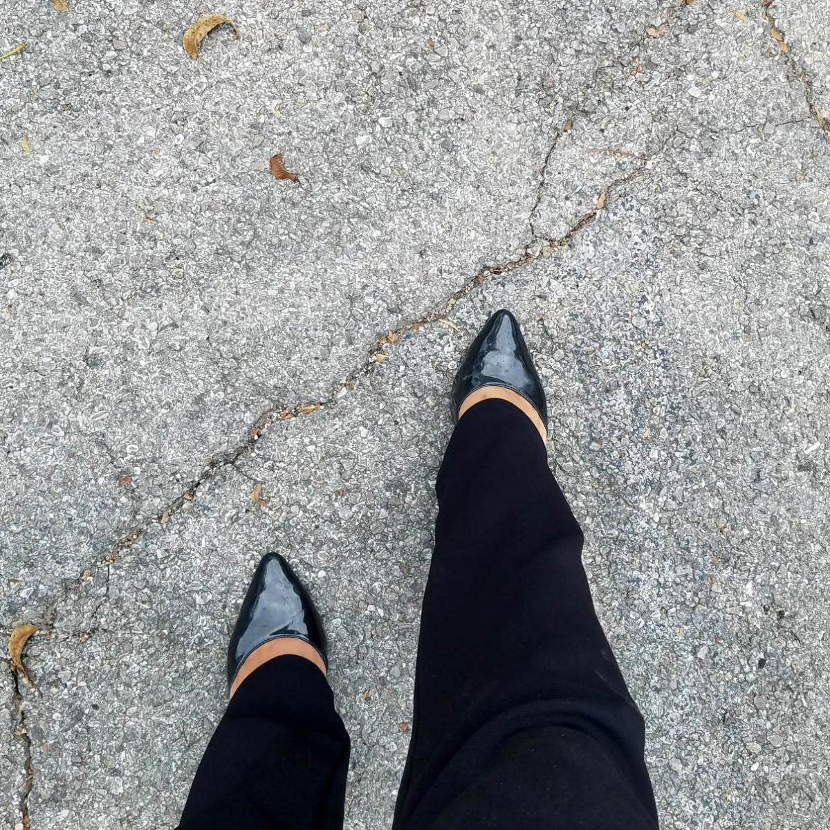 Person's feet walking on concrete wearing black pointy shoes.