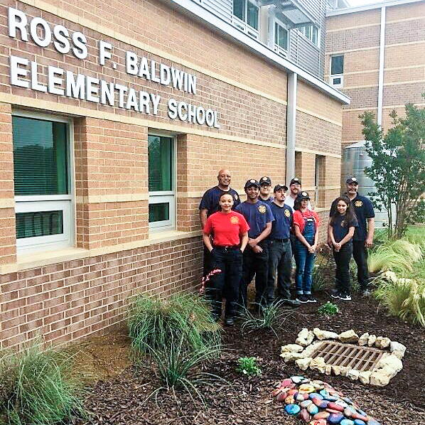Group photo of firefighters and firefighters-in-training that built a garden at Baldwin Elementary. Photo is taken in the garden area.