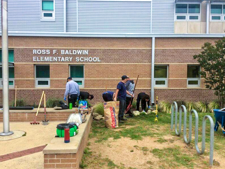 Firefighters working on building a garden in front of Ross F. Baldwin Elementary School.