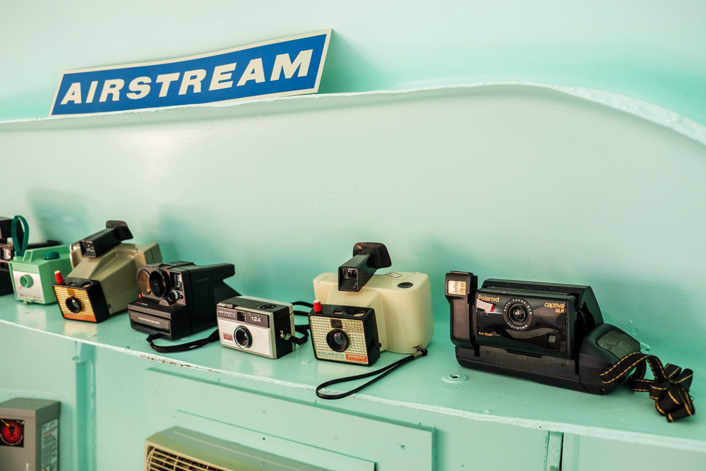 "Photo of a teal shelf with several old cameras on it. A sign above reads ""Airstream"""