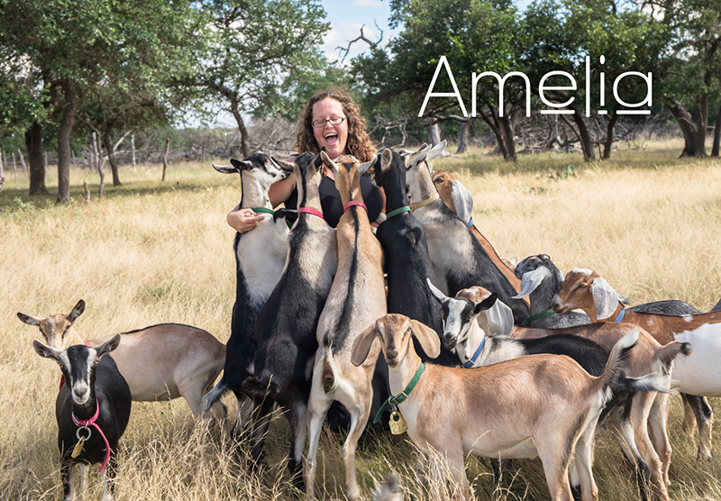 Amelia surrounded by goats on her farm.