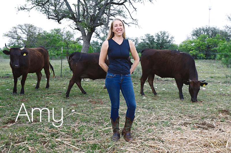 Amy on her farm with cows in the background.