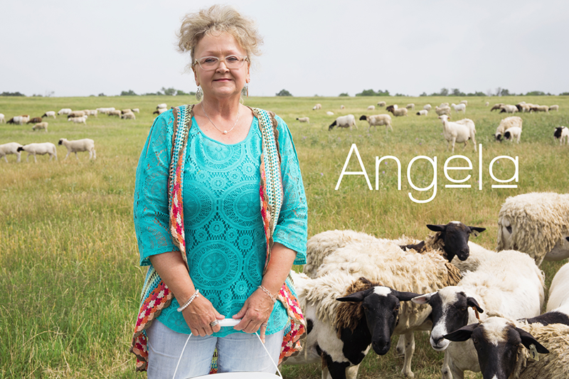 Angela on her farm with livestock in the background.