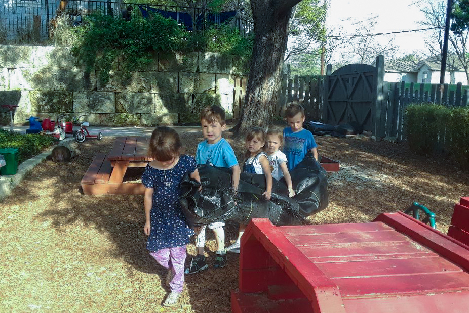 Kids carry a tarp through the schoolyard.
