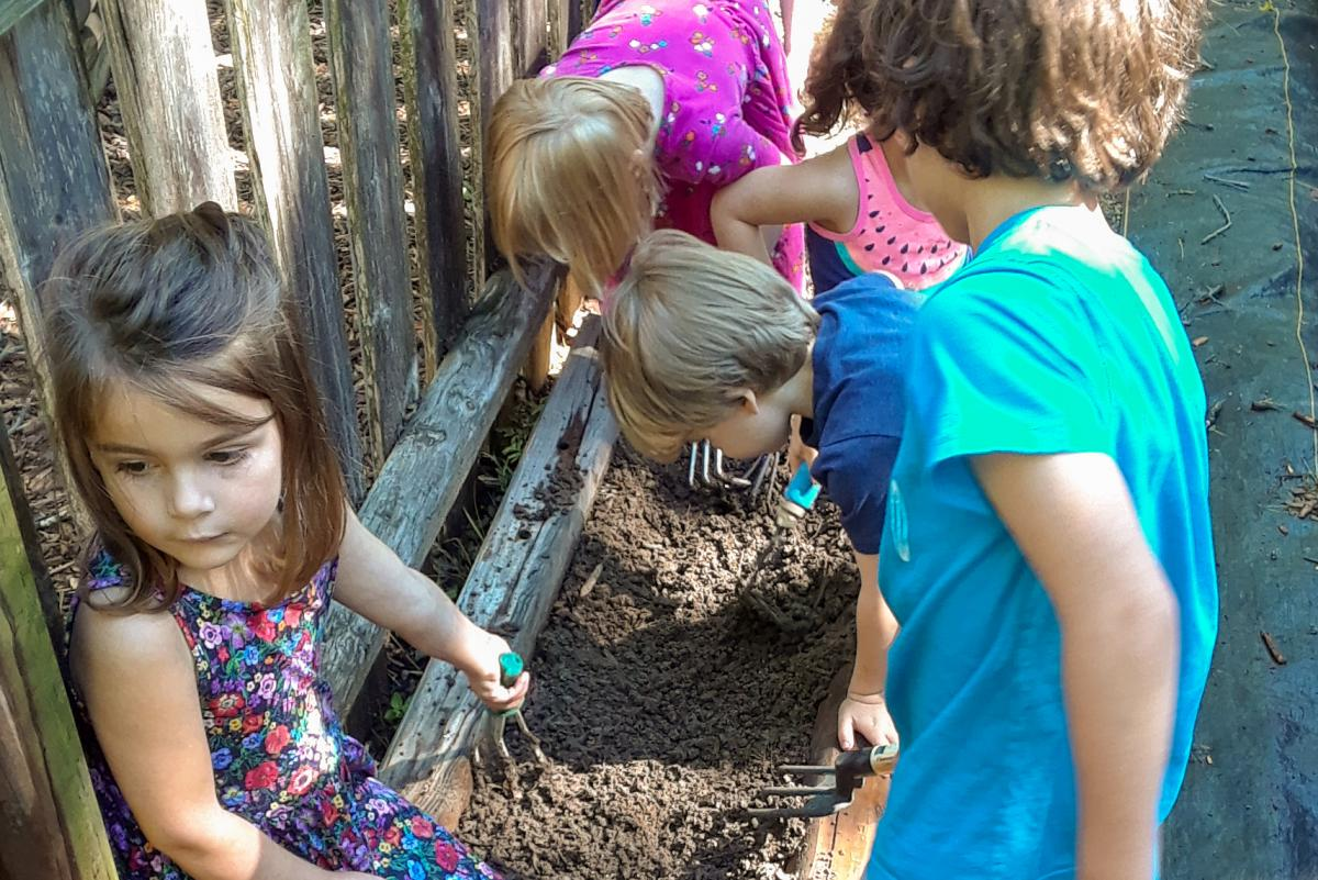 Kids are digging and planting in mini-gardens.