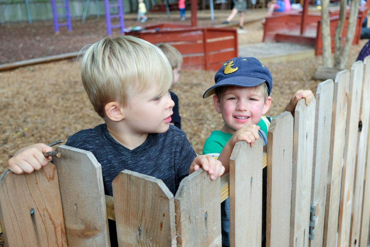 Two little boys look out from over a fence. One is wearing a blue hat and smiling at the camera.