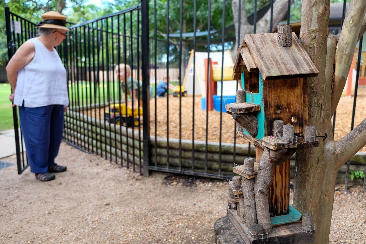 Teacher speaks with student through a black metal gate. In the foreground, there is a multi-tiered bird house.