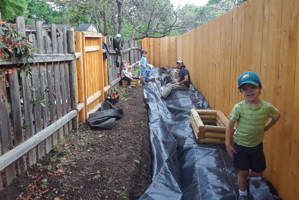 Kids stand in the trench area where they are planting a garden.