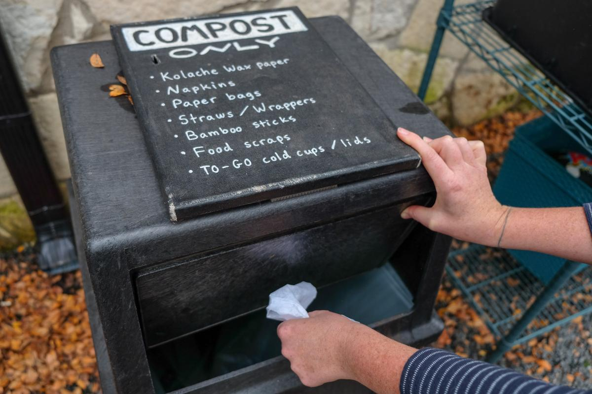 "Photo of compost bin and person's hand placing an item in it. Bin reads ""Compost only"""