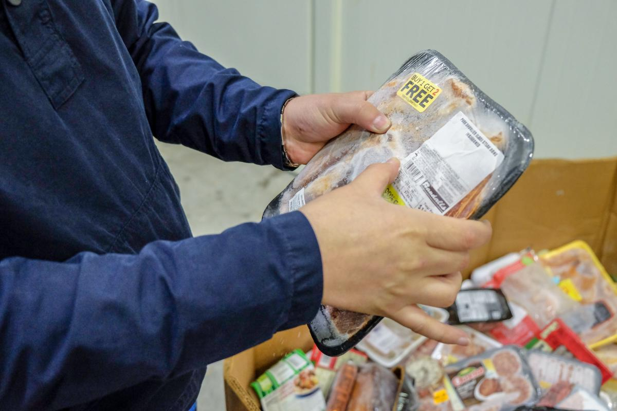 Person holding package of meat.