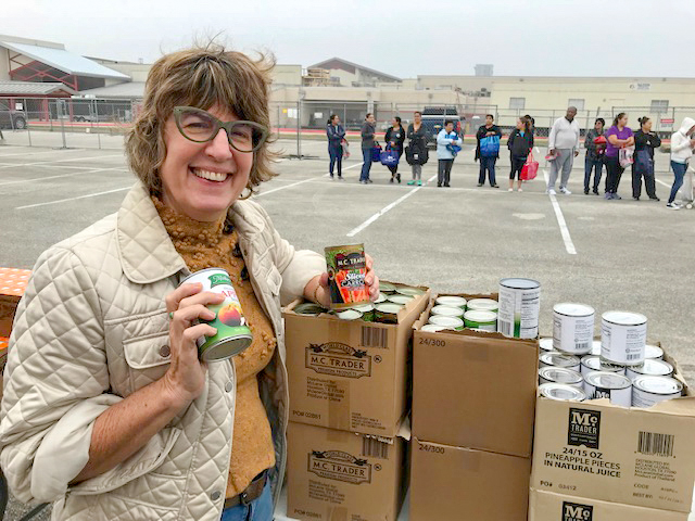 Chief Sustainability Officer Lucia Athens holding a couple of cans and smiling at the camera. There is a line of folks behind her.