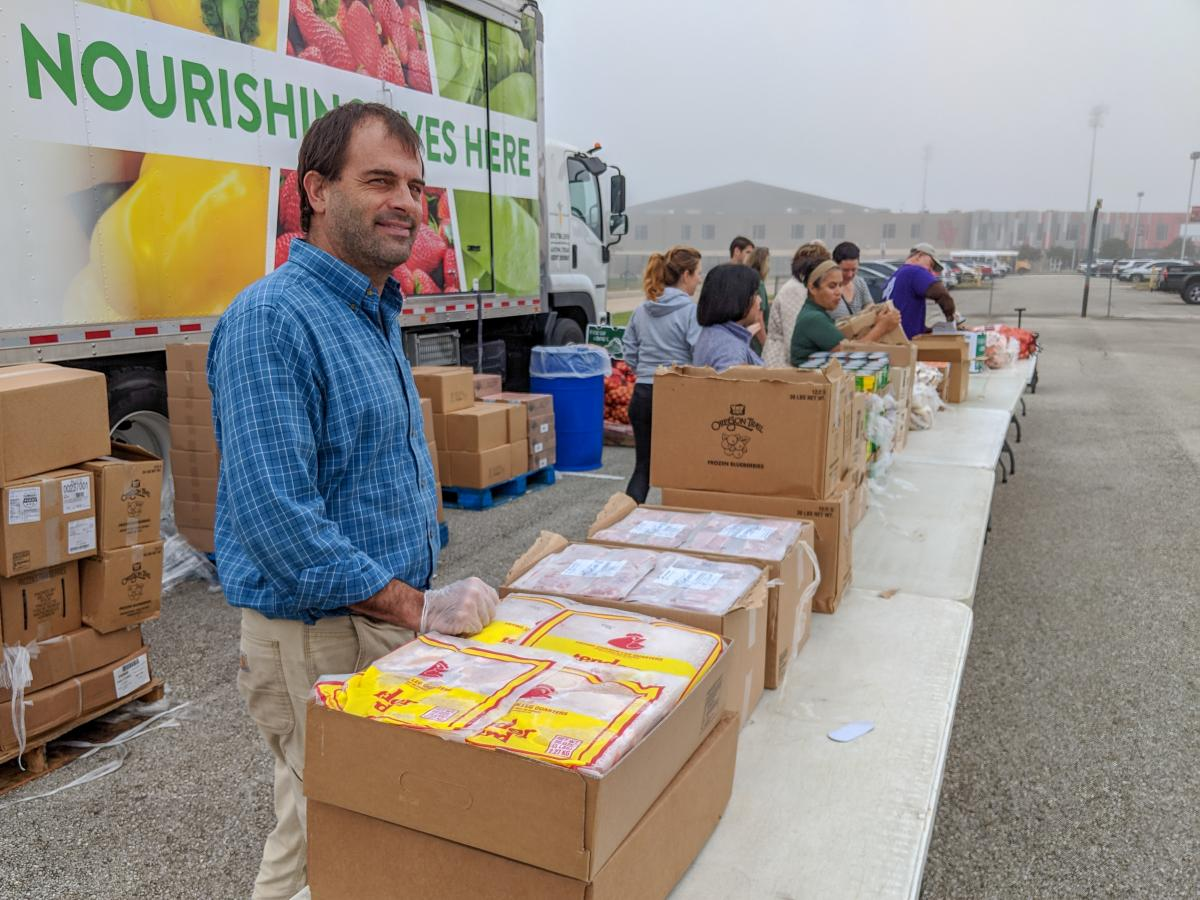 Food Policy Manager Edwin Marty stands at a distribution table ready to pass out frozen meat.