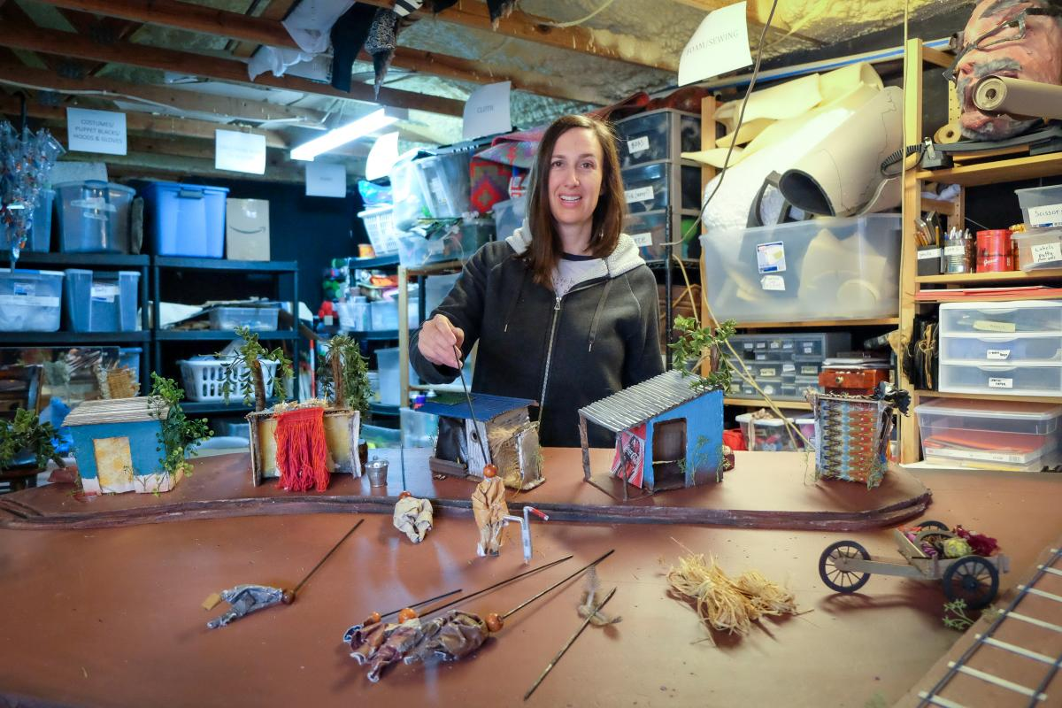 Caroline in her workshop holding a tiny puppet.